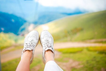 Close-up of female legs in sneakers in mountains on the cable car Stock Photo
