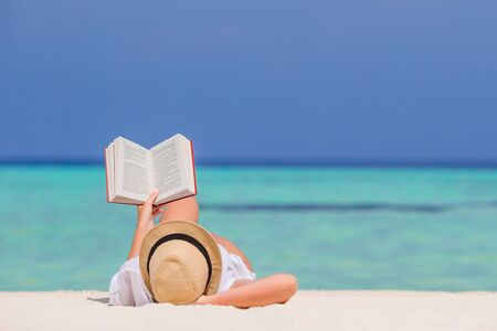 Young person reading book while lying on white tropical sand beach
