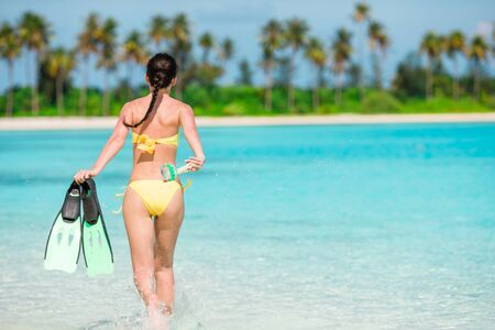 Beautiful girl with equipment for snorkeling have fun on the beach