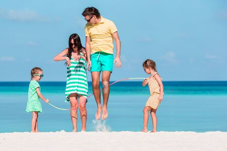 Happy family playing together on white beach Imagens