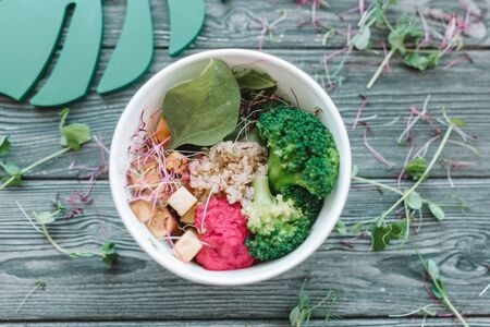 Bowl of bright healthy vegan lunch: vegetable salad with tofu, hummus and broccoli