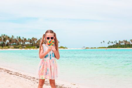 Adorable little girl with lollipop on tropical beach Reklamní fotografie