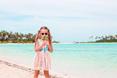 Entzückendes kleines Mädchen mit Lutscher am tropischen Strand Standard-Bild