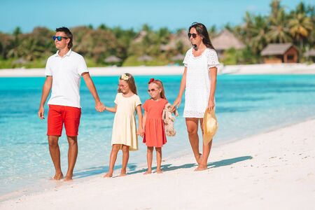 Happy family with kids walk on the beach at sunset Imagens