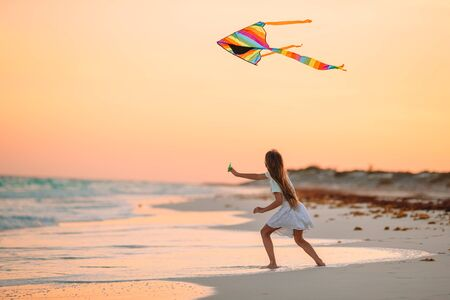 Little running girl with flying kite on tropical beach. Kid play on ocean shore.