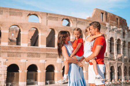 Happy family in Europe. Parents and kids in Rome over Coliseum background