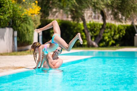 Happy family having fun together in outdoors swimming pool