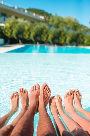 Close up of four peoples legs by pool side