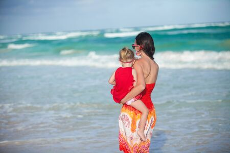 Back view of mother and daughter in red dress walking on beach Stock Photo