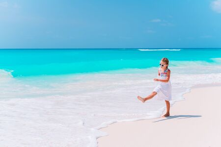 Beautiful little girl in dress and hat at beach having fun. Adorable girl enjoy summer vacation Banco de Imagens