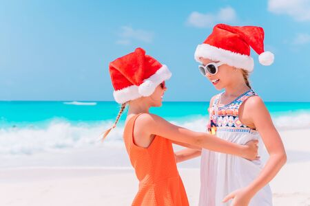 Little adorable girls in Santa hats having fun anad fooling at Christmas on the beach Banco de Imagens