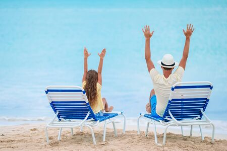 Happy father and his adorable little daughter on the beach relax on the loungers Stockfoto
