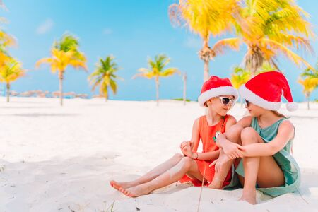 Little adorable girls in Santa hats having fun anad fooling at Christmas on the beach Imagens