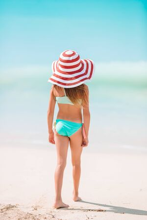 Back view of little girl in red hat on tropical beach