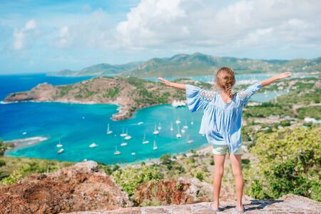 Adorable little kid enjoying the view of picturesque English Harbour at Antigua in caribbean sea. View of paradise bay at tropical island in the Caribbean Sea Stock Photo