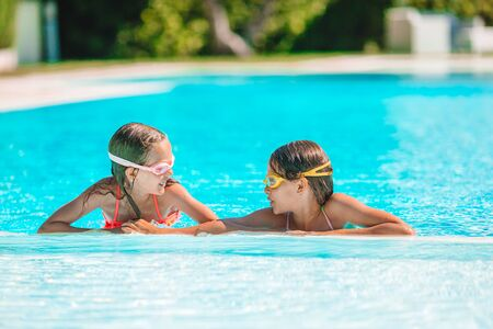 Adorable little girls playing in outdoor swimming pool on vacation