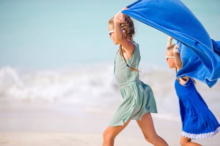 Little girls fooling on the beach on summer vacation