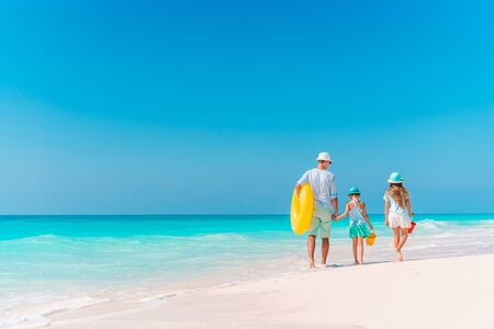 Father with kids on the beach going to swim. Family vacation Stock Photo