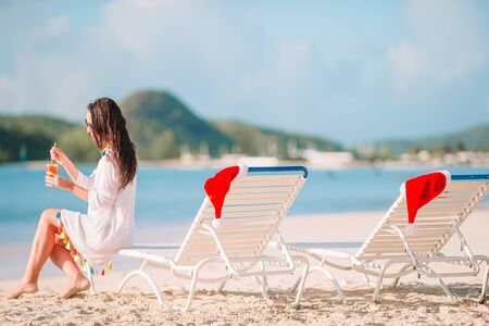 Young woman with cocktail glass relaxing on the beach