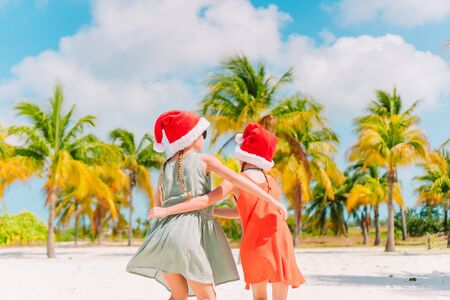 Little adorable girls in Santa hats during beach Christmas vacation having fun together Stok Fotoğraf