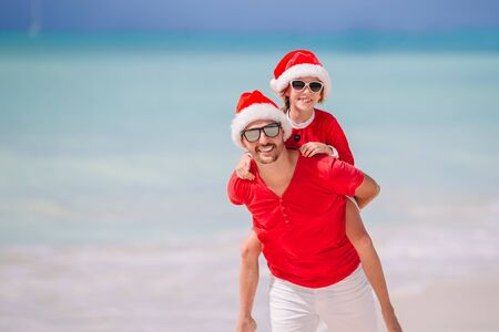 Father and daughter in Santa Hat have fun at tropical beach