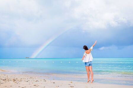 Beautiful woman on the beach with beautiful rainbow over the sea