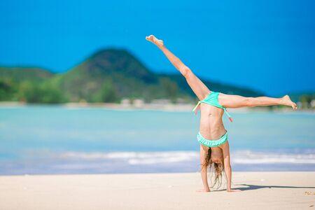 Aktives kleines Mädchen am Strand, der viel Spaß hat. Sportliches Kind macht sportliche Übungen an der Küste