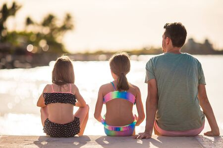 Young family of dad and kids enjoying beach summer vacation on the bridge Banco de Imagens