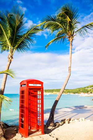 Red phone booth in Dickenson's bay Antigua. Beautiful landscape with a classic phone booth on the white sandy beach in Antigua