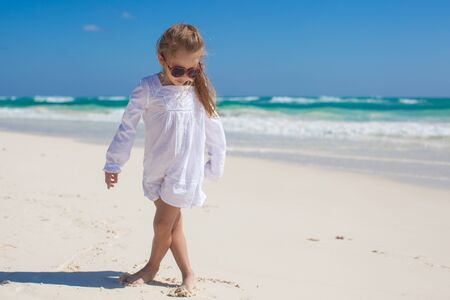 Adorable little girl in beautiful clothes dancing at tropical beach