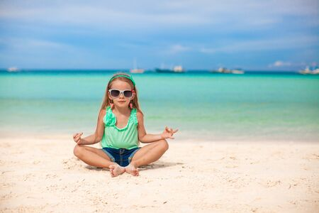 Beautiful little girl sitting in a lotus position on an exotic beach Stock Photo