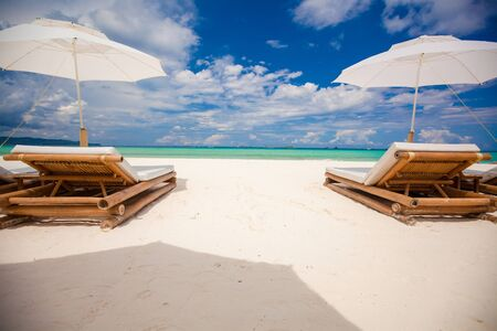 Fantastic view of nice tropical empty sandy beach with umbrella and beach chair