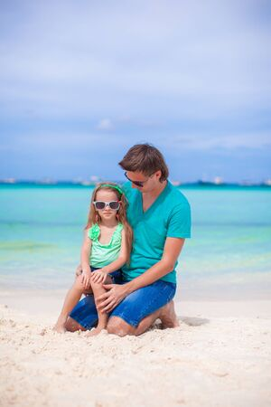 Young father and his little daughter sitting on tropical white sand beach