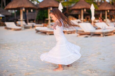 Adorable little girl in beautiful clothes dancing at sunset beach Stock Photo