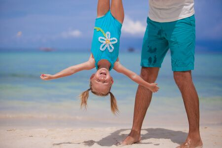 Father holding his happy smiling daughter upside down on sandy beach