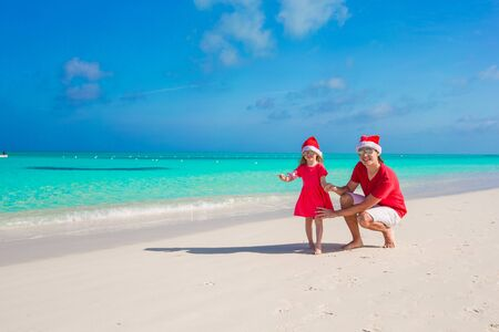 Young father and adorable little daughter in Christmas Hat Stock Photo