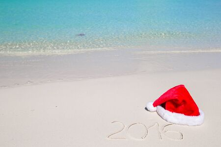 Merry Christmas written on tropical beach white sand with red xmas hat