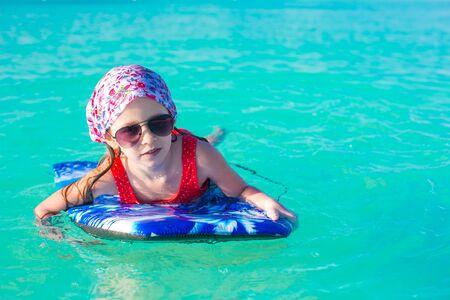 Bambina carina che nuota su una tavola da surf nel mare turchese