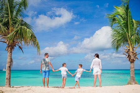 Happy beautiful family of four on the beach Фото со стока