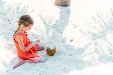 Little adorable girl with big coconut on the beach Banque d'images - 133779707