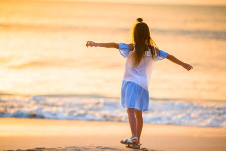 Adorable happy little girl walking on white beach at sunset. Banque d'images - 133779720