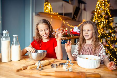 Little girls making Christmas gingerbread house at fireplace in decorated living room. Banque d'images - 133779749