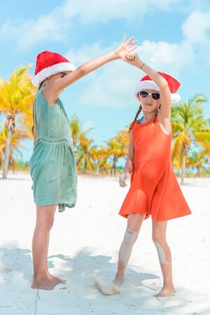 Little adorable girls in Santa hats during beach vacation have fun together Banque d'images - 133779787