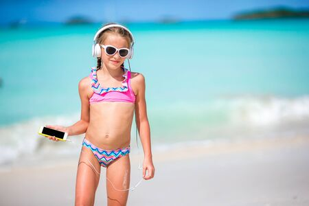 Little girl with headphones on the beach Banque d'images - 133779796