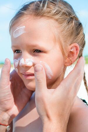 Father applying sun cream to daughter nose. Banque d'images - 133779792