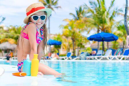 Kleines Mädchen mit einer Flasche Sonnencreme, die am Rand des Swimmingpools sitzt