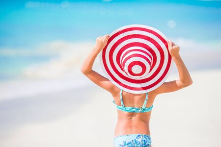 Little girl in big red hat on the beach during caribbean vacation