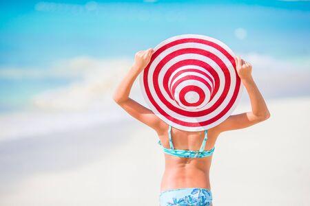 Niña con gran sombrero rojo en la playa durante las vacaciones en el caribe
