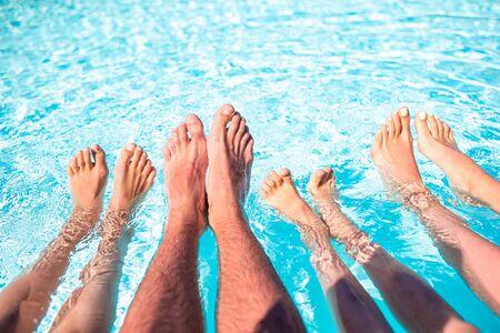 Family legs underwater in the swimming pool outdoors Standard-Bild