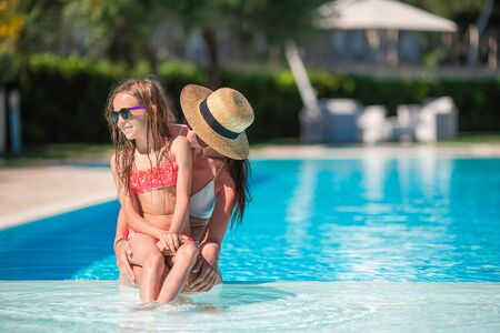 Family of mom and little daughter enjoying summer vacation in luxury swimming pool